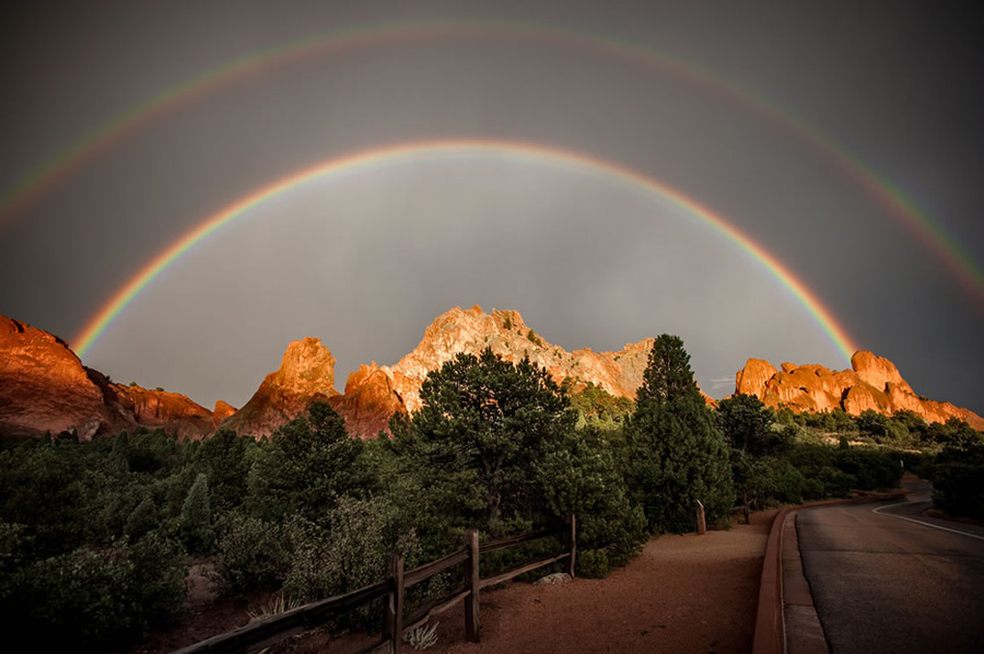 """Double rainbow over Garden of the Gods in Colorado Springs, CO. Did you know there really isn't an """"end"""" to a rainbow? Maybe that's why finding a pot of gold is as hard as spotting a tricky leprechaun. If you stood at where I can see the """"proverbial"""" end of the rainbow, then that rainbow would appear to you to be in a different spot. It's one of nature's very best optical """"illusion"""" tricks. Experiencing the phenomenon depends upon where you are standing, where the sun is and where the moisture is just right in the air. Rainbows, especially double rainbows, are considered a positive, awe-inspiring sign in most cultures. Photo #1 by Raymond Larose"""