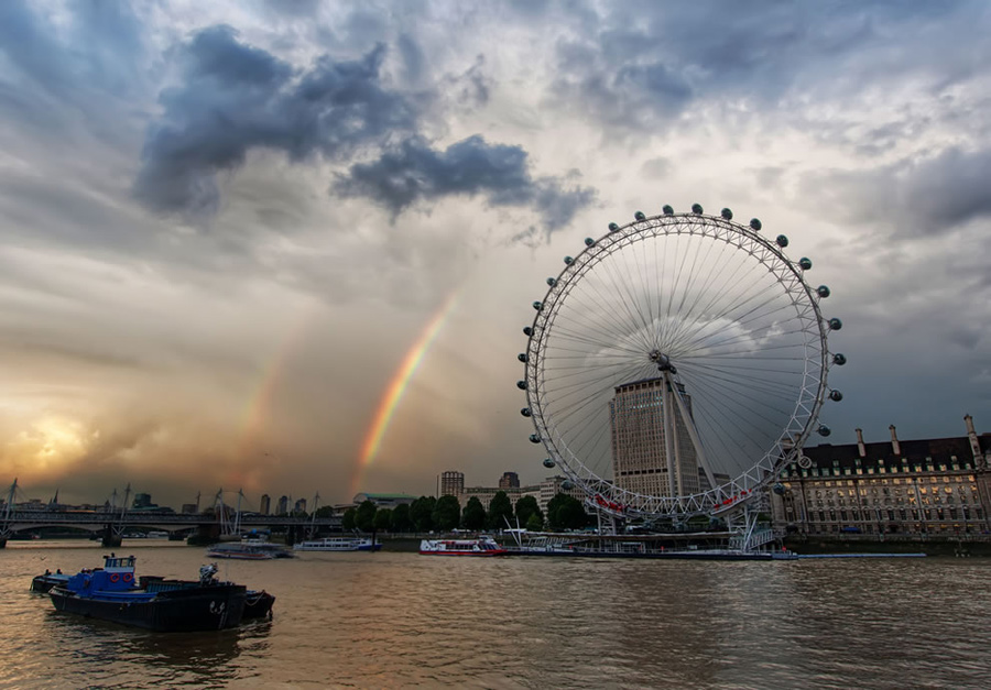 """Double rainbow over the London Eye. Accuweather wrote, """"Nature's natural color spectrum always elicits the same pattern (red, orange, yellow, green, blue, indigo, violet) when light is refracted. While a primary rainbow is visible when light is reflected once off the back of a raindrop, a secondary and usually dimmer rainbow is spotted when light is reflected twice in a more complicated pattern. The colors of the second rainbow are inverted, with blue on the outside and red moved to the inside. The second bow appears dimmer or cloudier because much more light is released from two reflections, and both bows cover a larger portion of the sky. It is rare and unlikely, but three or even four rainbows can be seen on occasion, but only if they are reflected off of the earthly objects."""" Photo #10 by Trey Ratcliff"""