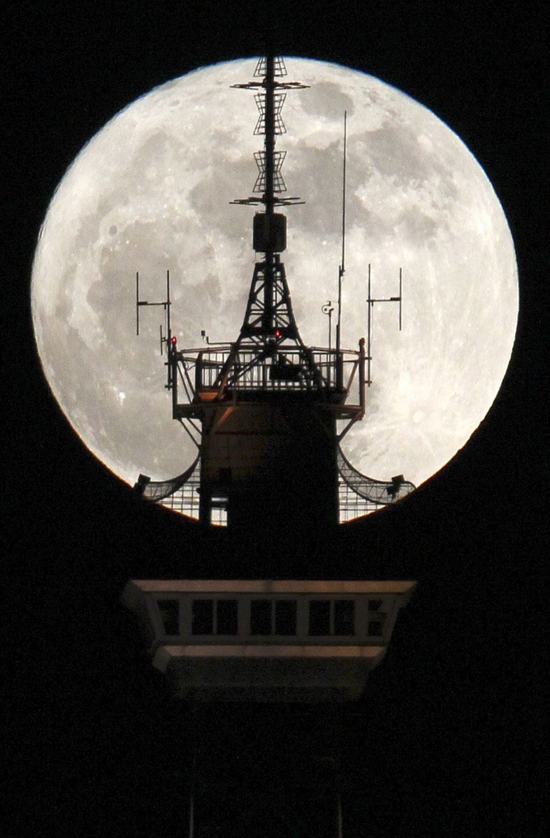 The moon is seen behind the top of the radio and television tower 'Funkturm' in Berlin