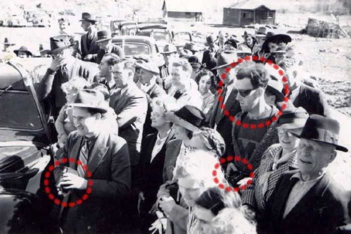 People believe that this photograph, taken in 1941 at the re-opening of the South Forks Bridge in Gold Bridge, Canada, is depicting a man in seemingly modern dress and style, with a camera that is advanced well beyond its time. The circle on the left illustrates a man with a camera typical to the time-period.