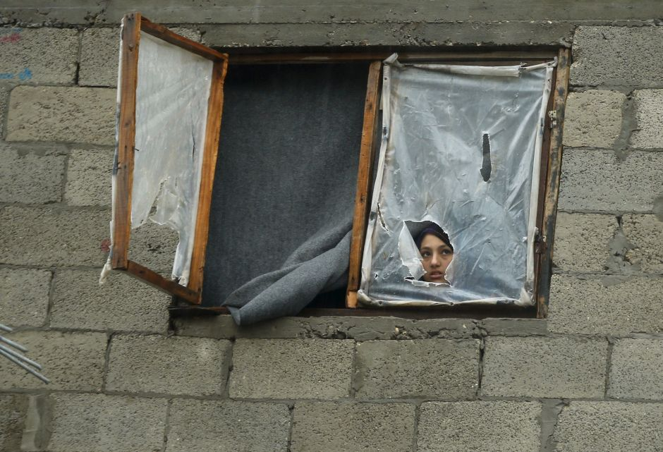 A Palestinian girl looks out the window of her family's house on a rainy day, in the northern Gaza Strip November 17, 2015. (Photo by Mohammed Salem/Reuters)